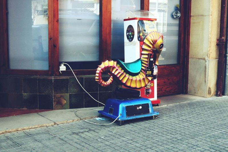 Electric toy and gumball machine on footpath