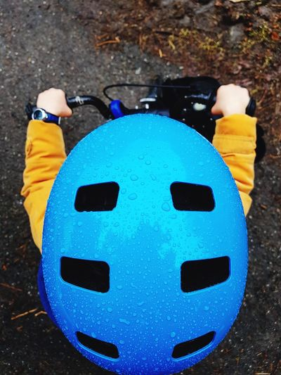 High angle view of child sitting on bicycle Young Child Sitting Bicycle Blue Waterdrops Rain Orange Helmet Top View