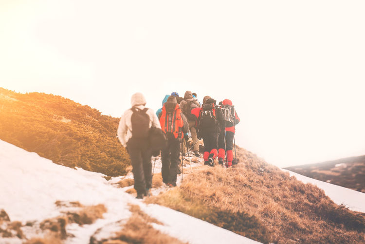 Low angle view of people walking on mountain against clear sky