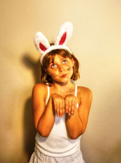 Girl in bunny costume standing against wall