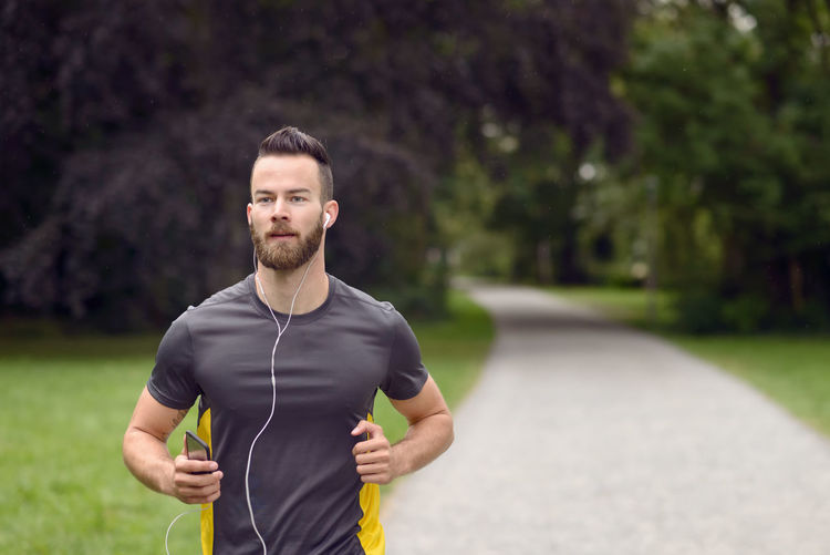 Fit bearded young man jogging through a park Active Athlete Athletic Beard Bearded Concept Earplug Evening Fit Fitness Male Man Morning Music One Person Outdoors Park Park - Man Made Space Runner Running Smartphone Sport Young