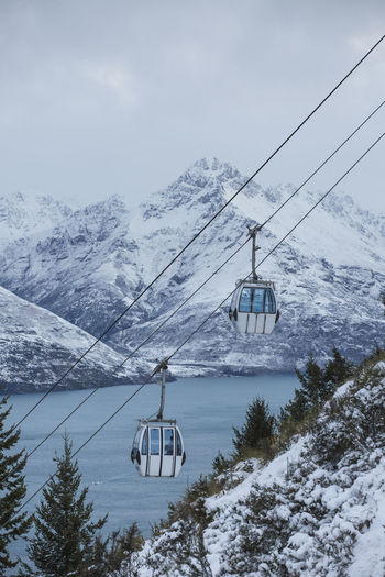 Overhead Cable Cars Hanging Against Lake And Mountains During Winter
