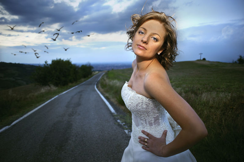 Portrait of beautiful young woman standing on road