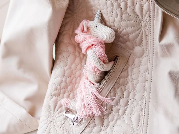 Cute fairy unicorn with pink mane. crocheted hand made toy in pocket of leather jacket. magic.