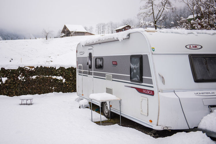 Architecture Beauty In Nature Caravan Caravaning Cold Temperature Covering Day Extreme Weather Field Land Land Vehicle Mode Of Transportation Mountain Nature No People Outdoors Scenics - Nature Snow Snowcapped Mountain Snowing Transportation Tree White Color Winter