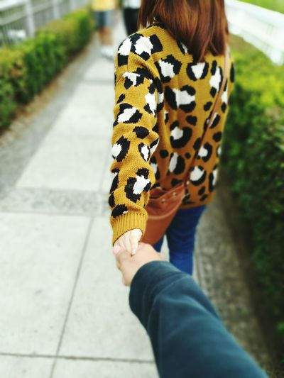 Cropped image of man holding woman hand at park