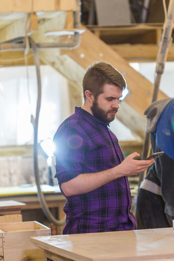 Man using smart phone in workshop