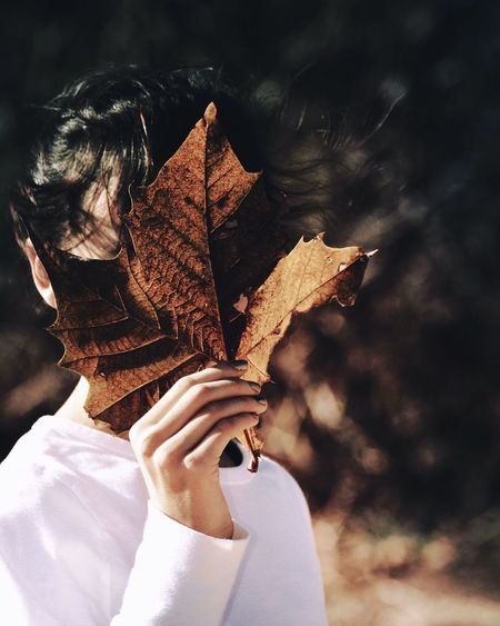 Close-up of woman covering face with dry maple leaf