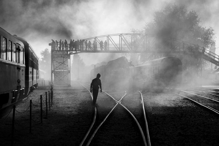 Rear view of man on railroad track against sky