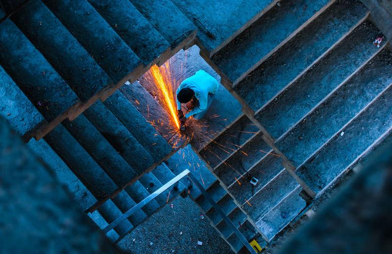 A worker is working with sparks. Working Work Worker Lifestyles Street Streetphotography Streetlife Colors Sparks Blue Background Building Construction Illuminated Blue High Angle View Pattern Architecture Close-up Office Building Spiral Staircase Spiral Steps And Staircases Stairway Geometric Shape Building