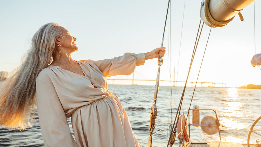 Senior woman standing on boat in sea during sunset