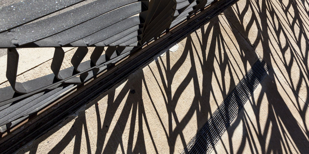 High angle view of shadow on railing against wall