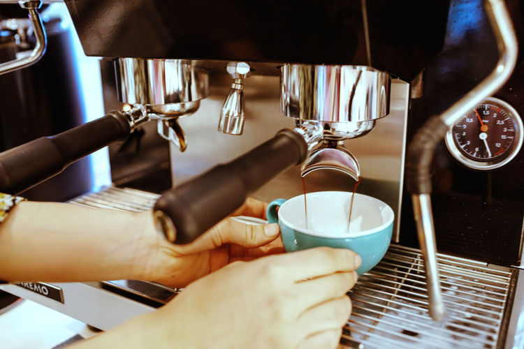 Midsection of woman holding coffee cup at cafe