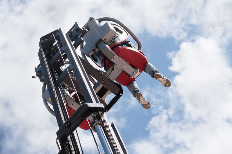 Low angle view of person sitting in ride against sky