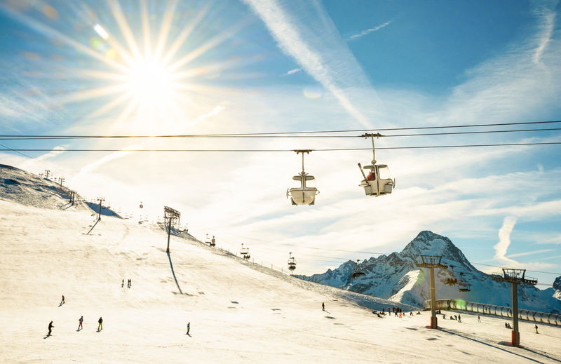 Ski Lift Over Snow Covered Field Against Sky