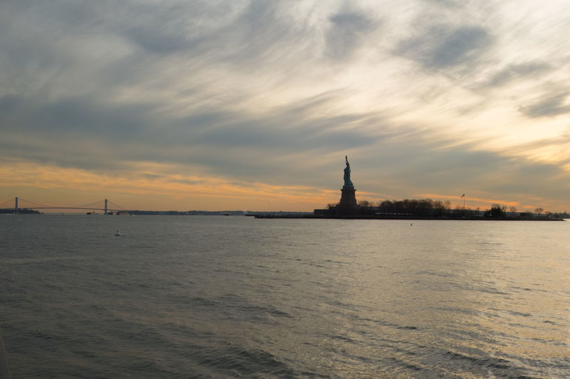 Statue of Liberty New York at sunset. Silhouette of the Statue of Liberty at sunset with wispy clouds and rippling ocean waves. Architecture Liberty Island Liberty Island Ferry New York New York City New York Harbor New York ❤ New York, New York No People Outdoors Sight Seeing Sightseeing Sky Statue Statue Of Liberty Statue Of Liberty New York Sunset Things To Do In New York Travel Destinations Water