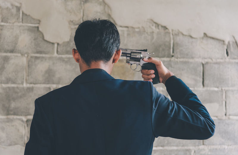 Rear view of man aiming gun to his head while standing against wall