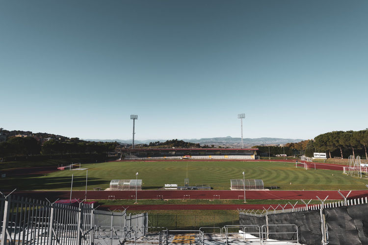small stadium Outdoors Absence Soccer Field Empty Plant Playing Field Team Sport Practice Training Contest Match Poles Dribbling Field Goal Seats Play Football Competition Running Implant Track Grass Small Cement Architecture Pylons Light Bleachers Steps View Landscape Panorama Mountain Range Nature Movement Athletic Soccer Stadium Sport Grandstand