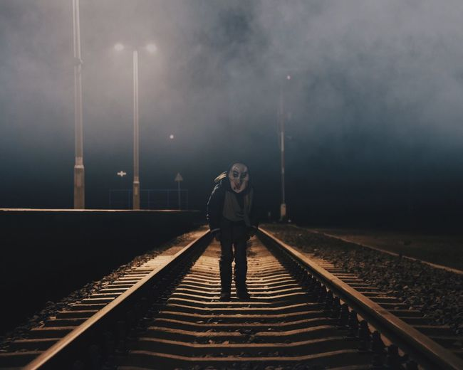 Man wearing spooky mask while standing on railroad track during halloween