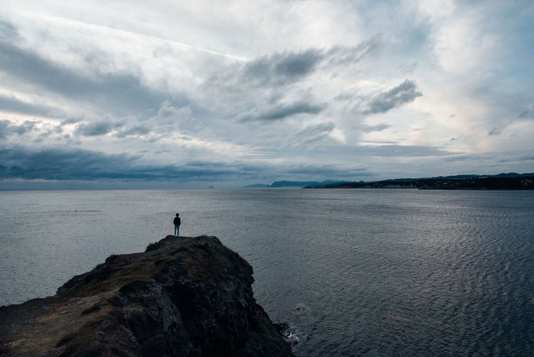 Silhouettes of people looking at the sea from a rocky spur. scenic view of sea against sky