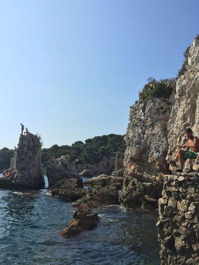 Man sitting on rocks by sea against clear sky