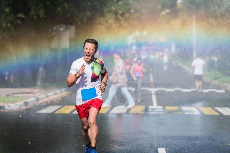 Full length of man running on road during rainfall