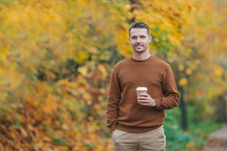 Portrait of smiling young man standing against trees during autumn