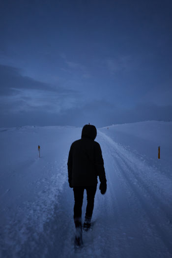 Rear view of silhouette man walking on snow covered landscape