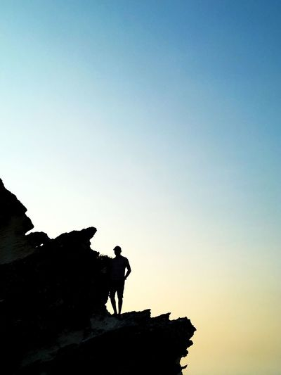 Low angle view of silhouette man standing on rock against sky