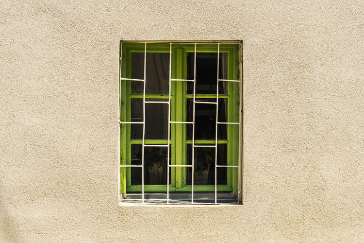 Old looking window isolated in the wall with white iron bars in front House Facade Shade Of Green Architecture Bars Building Exterior Built Structure Close-up Closed Window  Curtains Day Green Color Green Window Iron Bars Nature No People Old Look Photography Old Painted Wall Old Window Frame Outdoors Paint Peeling Rustic Window Single Window In The Wall Wall Paint Window Wooden Window