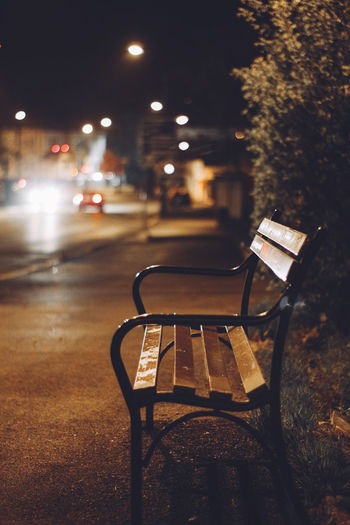 Empty chairs and table in city at night