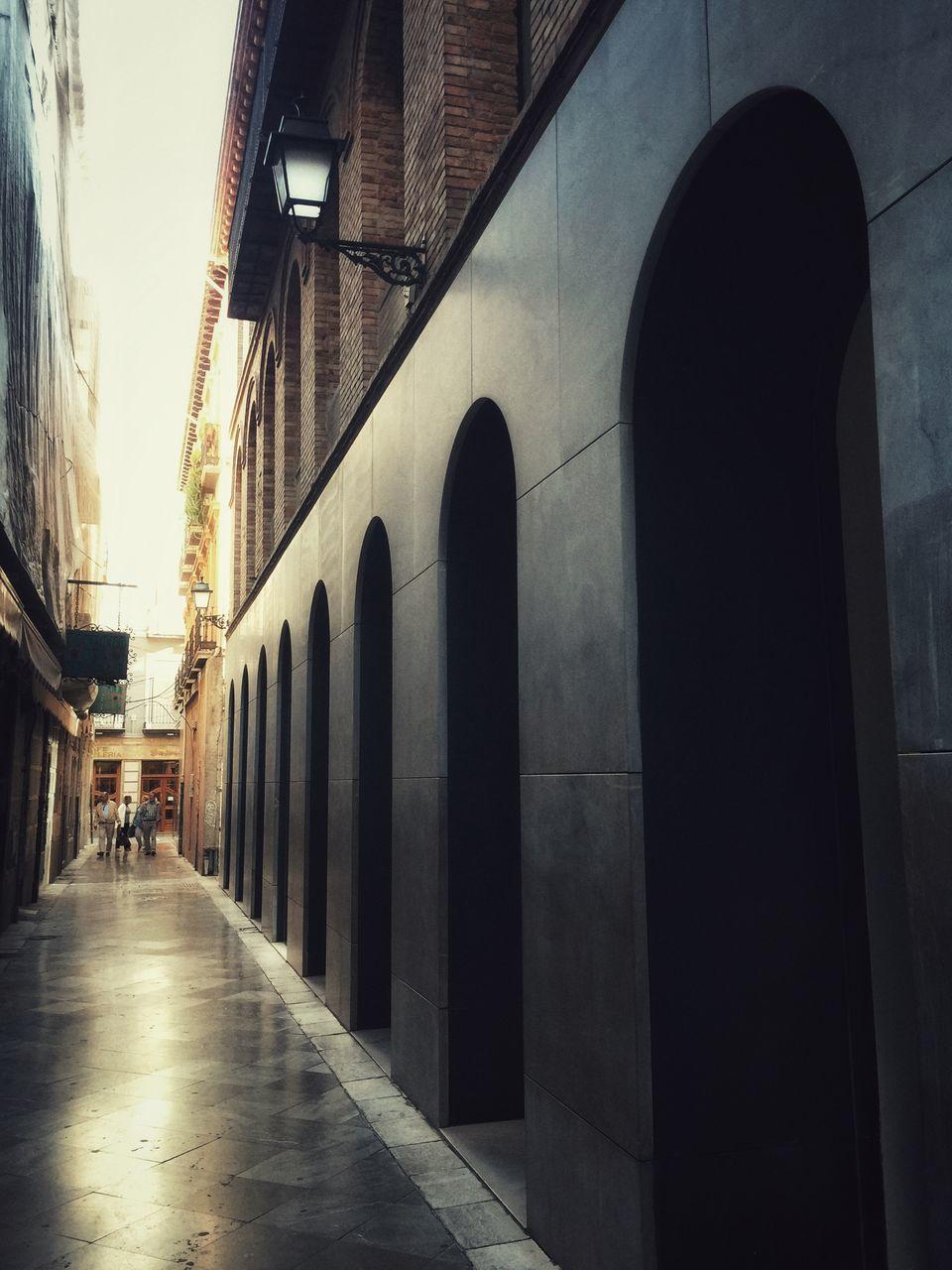 REAR VIEW OF MAN WALKING ON FOOTPATH AMIDST BUILDINGS