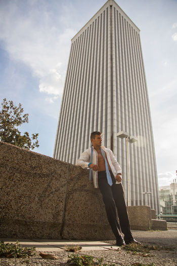 Man standing against modern building in city