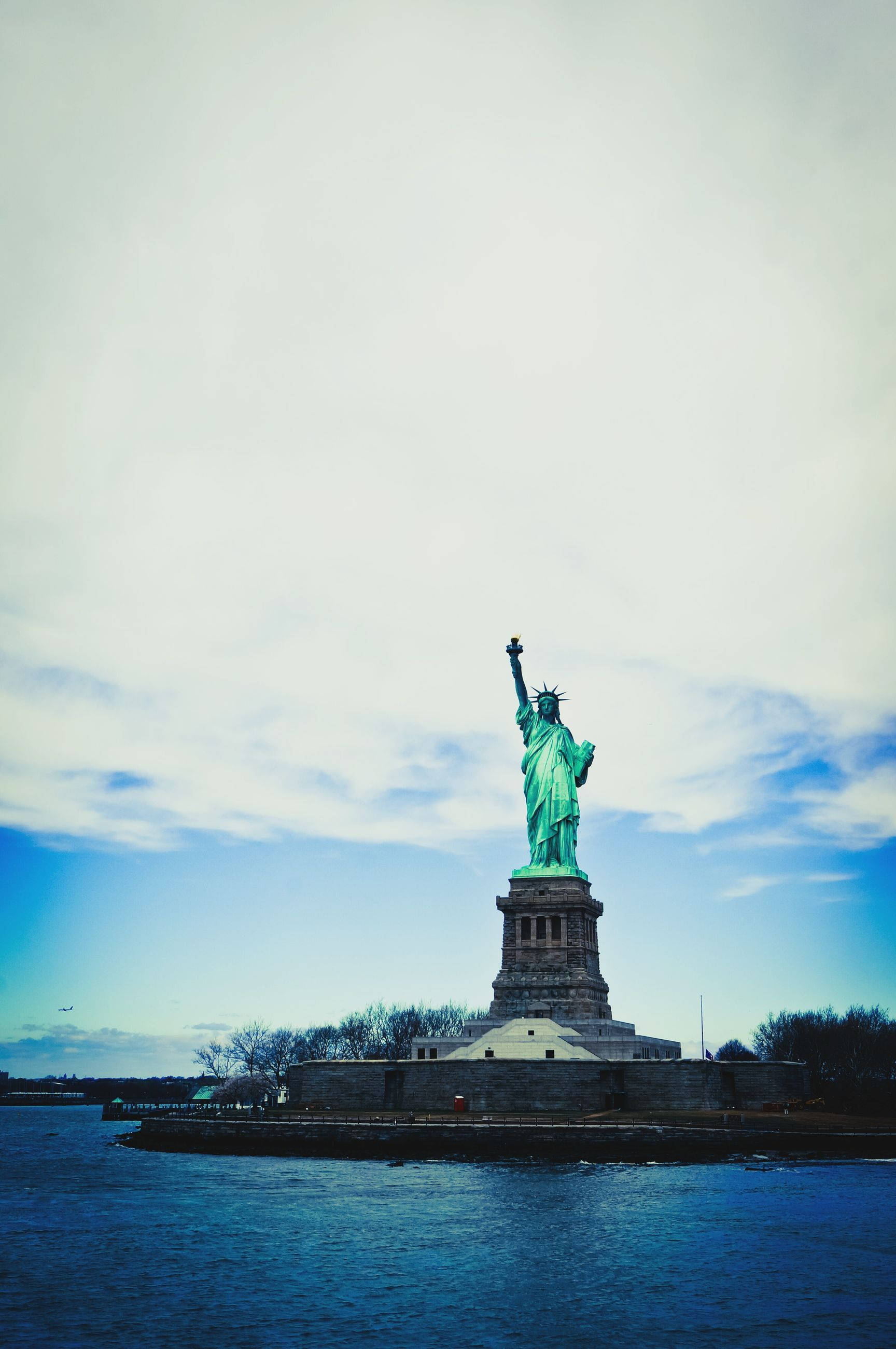 statue, human representation, sculpture, art and craft, art, creativity, water, animal representation, sky, waterfront, statue of liberty, cloud - sky, low angle view, famous place, travel destinations, international landmark, travel, built structure