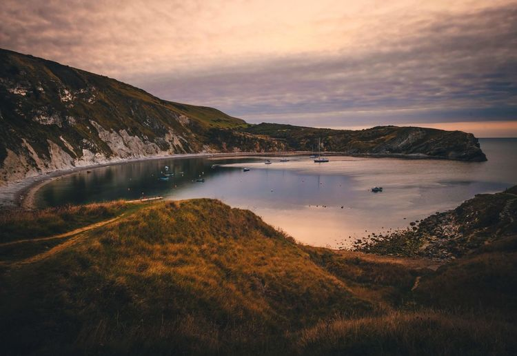 Scenic view of lulworth cove against sky during sunset