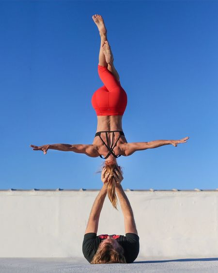 Man And Woman Acrobats Performing Stunt On Field Against Clear Blue Sky