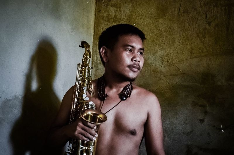 Man Holding Saxophones While Standing Against Wall At Home