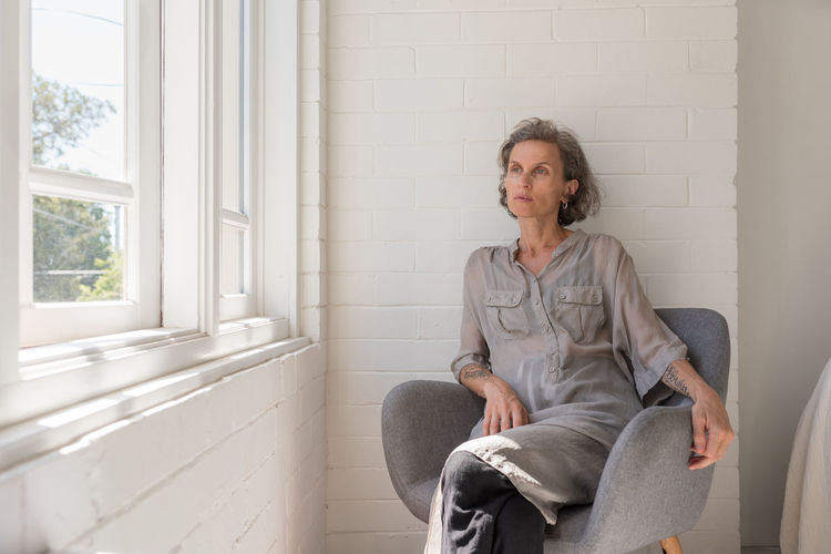 Tired middle aged woman One Person Sitting Three Quarter Length Chair Indoors  Front View Seat Casual Clothing Window Adult Lifestyles Real People Day Mature Adult Looking Away Armchair Domestic Room Portrait Contemplation Mature Women Women