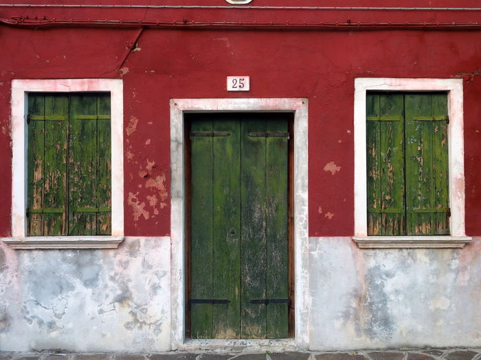 Green door and windows on red wall