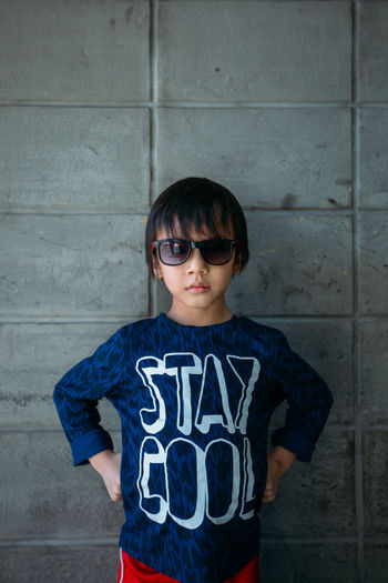 Serious Boy With Sunglasses Against Wall