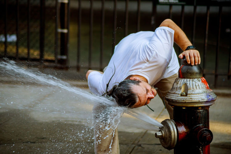 Man Washing Head In Flowing Water From Fire Hydrant In City