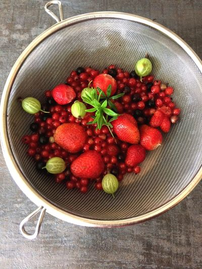 Directly above view of berry fruits in colander on table