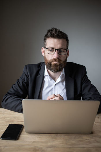 Mid adult man using smart phone while sitting on table