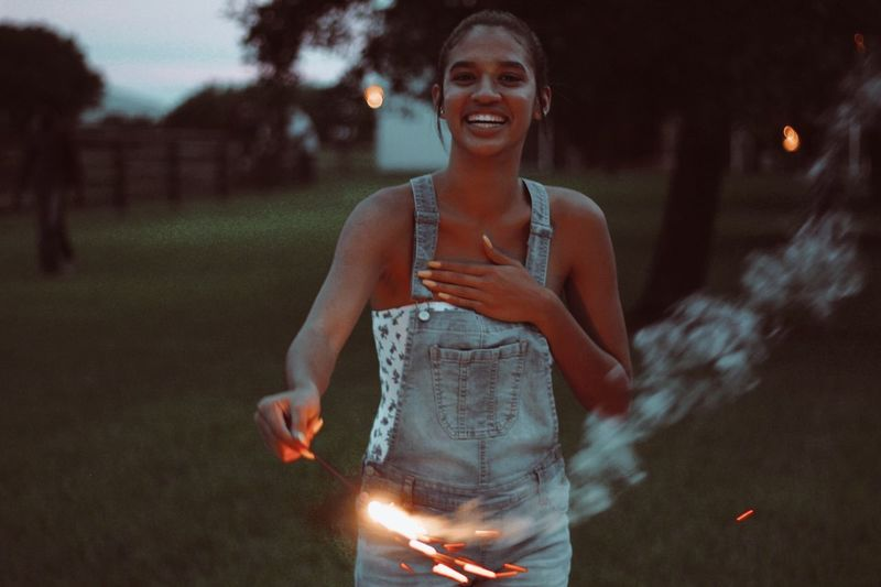 Portrait of smiling young woman burning sparkler outdoors