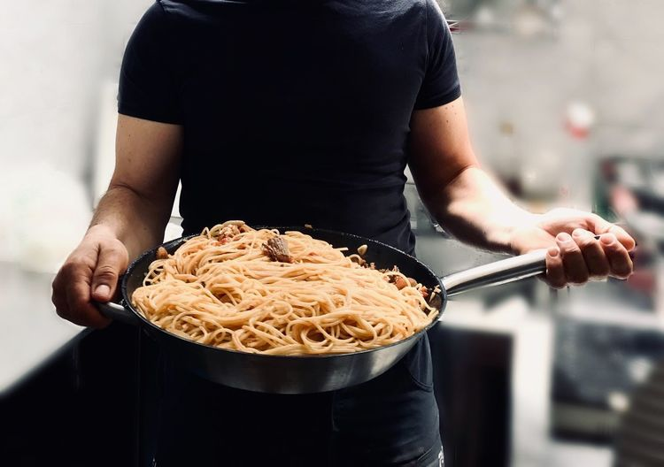 Midsection of man holding spaghetti