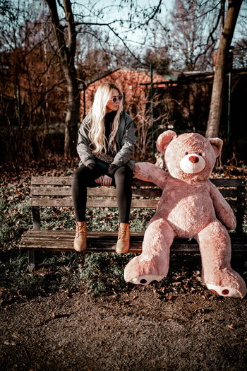 Full Length Of Woman With Teddy Bear Sitting On Bench In Park