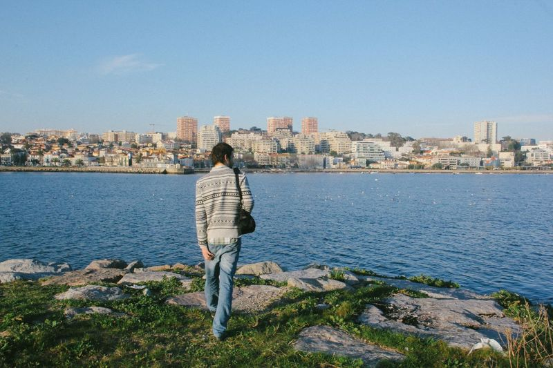 Rear view of man standing by sea against city