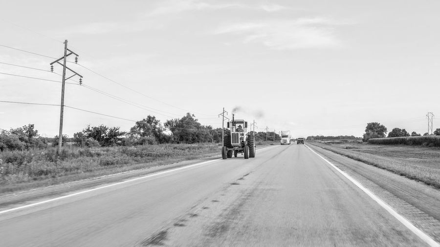 Person driving tractor on road against sky