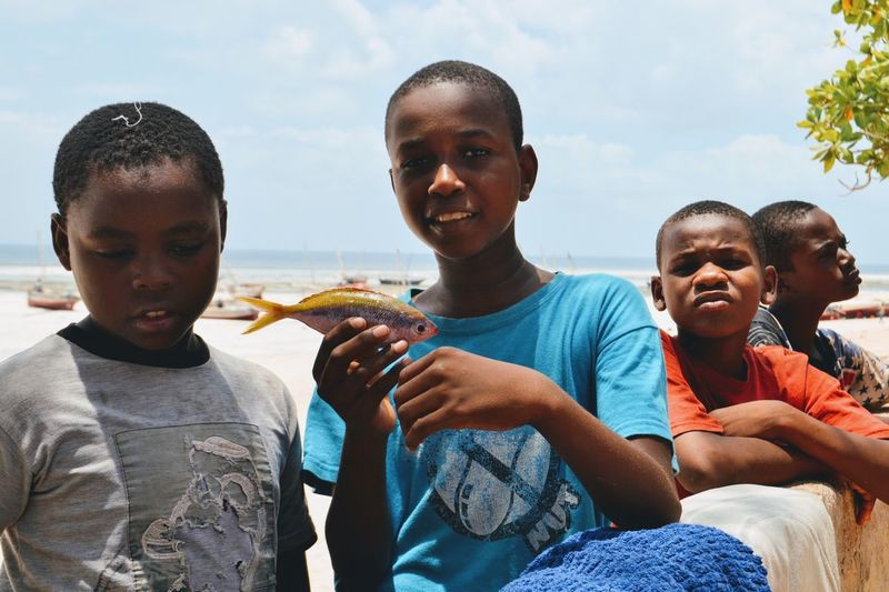 Portrait Of Smiling Boy Holding Dead Fish By Friends At Beach