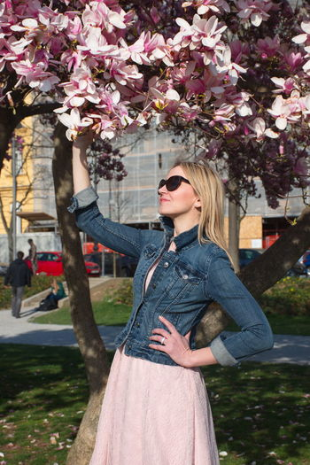 Plant Flowering Plant Flower Tree One Person Fashion Young Adult Standing Leisure Activity Nature Growth Three Quarter Length Day Young Women Women Lifestyles Hair Real People Hairstyle Beautiful Woman Springtime Outdoors Jeans Portrait Sunglasses Magnolia Blooming Pink Color Grass Park